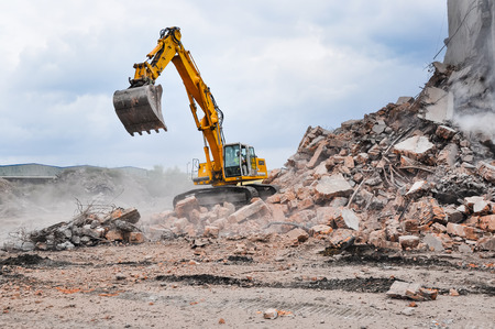 Excavator working at the demolition of an old industrial building. Foto de archivo