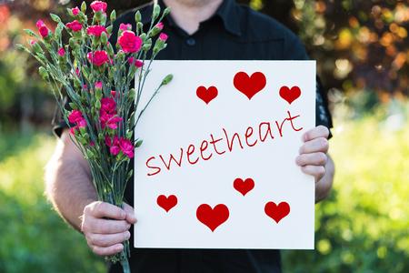 Man holding flowers and board - sweetheart 版權商用圖片