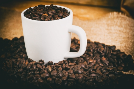 Aromatic coffee beans in a white mug on the board