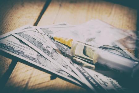Drug use and prohibited substances. The purchase of drugs. Dollars, syringe, needle and ashes.