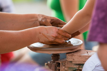Female hand helping to make ceramic jug on a wheel childrens hands. Stock Photo