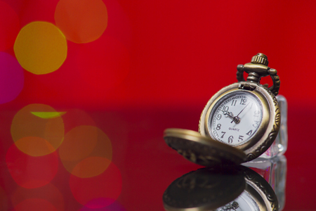 Photo of opened old vintage pocket clock against the light bokeh background
