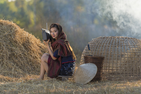 Asian beautiful girl wearing thai traditional dress,lying and listen radio on the straw. Stock Photo