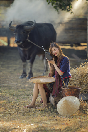 Asian woman listening radio with her buffalo, Thailand