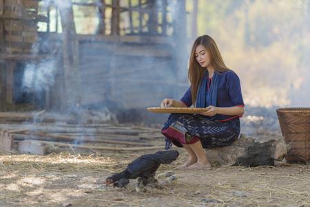 Asian beautiful girl winnowing rice separate between rice and rice husk Stock Photo