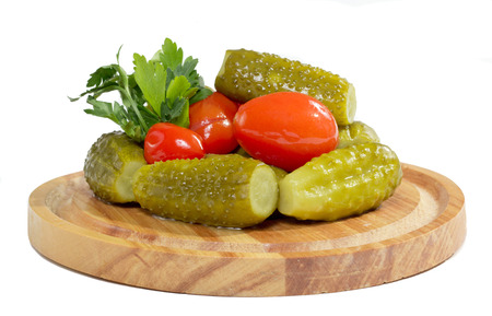 Pickled cucumbers and tomatoes on the wooden plate isolated on white background   photo