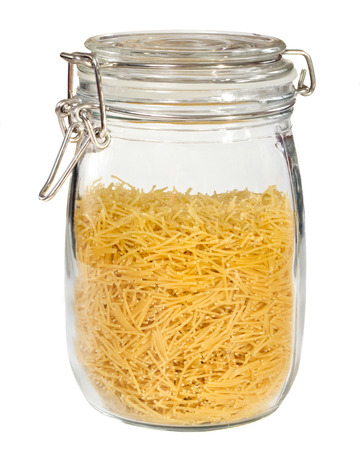 Pasta in glass jar isolated on white background photo
