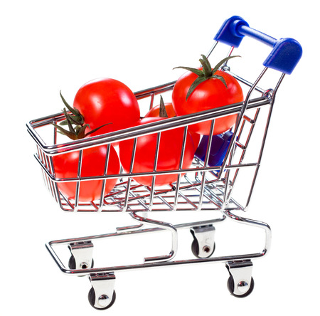 Shopping cart with cherry tomatoes isolated on white background photo