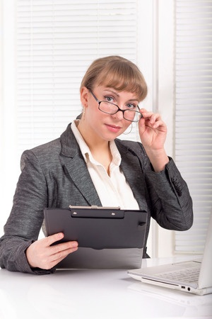 Business woman with glasses dressed in a formal suit sitting at her desk photo