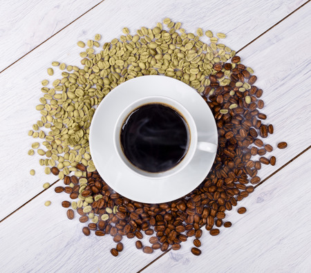 unroasted: Coffee cup on coffee beans on wooden table