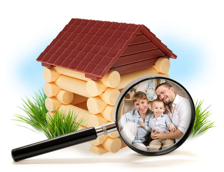 Happy family in a wooden house under magnifying glass photo