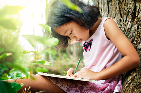 verry: Asian little girl sitting under a tree and writing a book. her it is verry cheerful Stock Photo