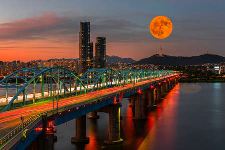 Twilight at Dongjak Bridge at Han river with full moon and seoul tower in Seoul City , South Korea