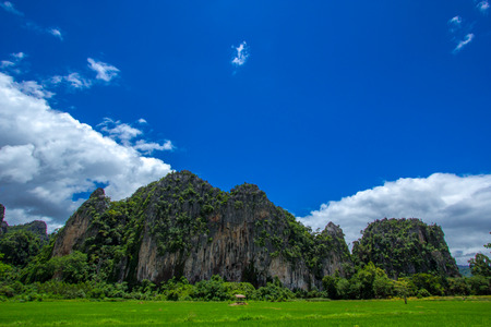 Paddy in front of the mountian and blue sky. Amphoe Noen Maprang is a new travel of Phitsanulok, Thailand