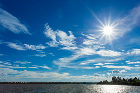 White clouds in dark blue sky background and water or river