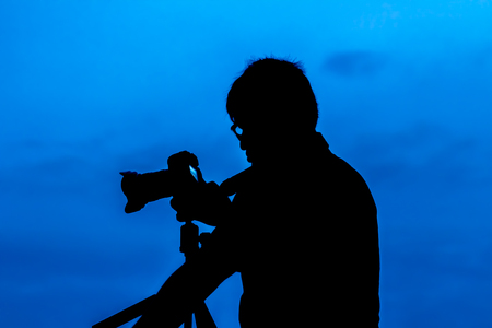 silhouette of man take a photo blue sky background