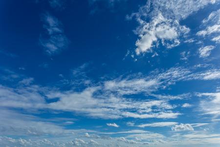 White clouds in dark blue sky background.