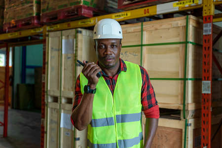 portrait of african american male factory warehouse foreman with safety vest and helmet working and using communication radio in storage warehouse of logistics business