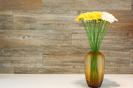 home accent: Gerbera flower on the vase wood backgrouds.