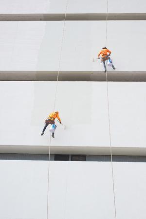 pintor: Pintores alto edificio de condominios en exteriores espolvorear con cuerda seguro seguro en Bangkok, Tailandia. Foto de archivo