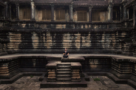 A Man Pray calm Adventure travellers sit on the wall at Angkor Thom Temple was the last and most enduring capital city of the Khmer empire , Siem riep, Cambodia