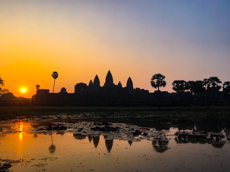 Silhouette Angkor Wat Temple with Rising Sun. Best time in the morning a popular view tourist attraction ancient temple complex Silhouette Angkor Wat with reflected in lake Siem Reap, Cambodia.