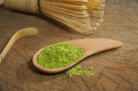 green powder: Powdered green tea on wood table. Stock Photo