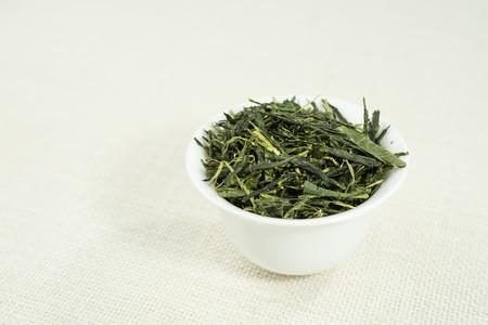sencha tea: Tea (Sencha) in white bowl on white background.