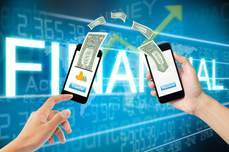 holding smart phone: mobile banking online money transfer concept with two hands holding smart phone and screen mobile phone transfer button, receive and dollar bills above on blue finance background. Stock Photo