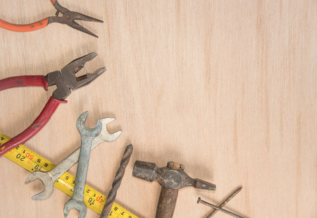 work tools hammer, wrench, screwdriver, pincers, pliers hand, screw, pliers old, spanner on a wooden table, top view with empty space Stock Photo