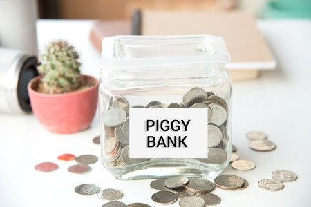 piggy bank, pile gold coin, with word text save money on paper in glass piggy bank.(business bank and finance concept)