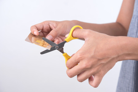 overspending: women hands holding scissors cutting credit card. bankruptcy finance concept Stock Photo