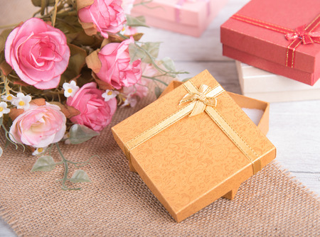 Vintage gift box and pink rose flower on wooden background Stock Photo