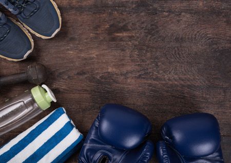 water shoes: Fitness with a bottle water, shoes,towel, headphones  and boxing gloves. Top View from above on wooden background. Stock Photo