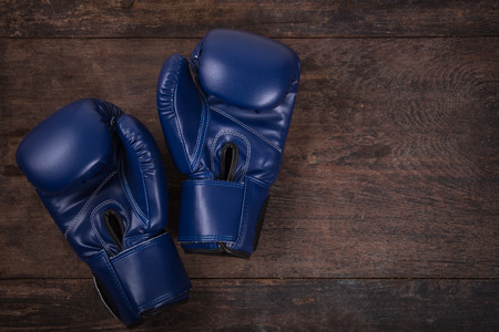 violence in sports: Fitness with boxing gloves. Top View from above on wooden background.