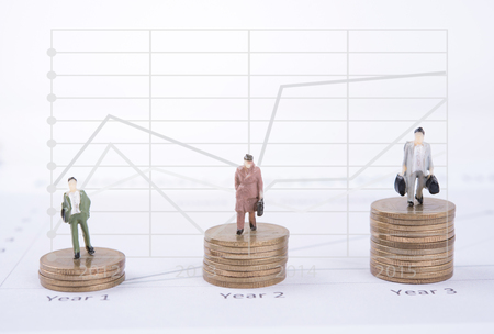 miniature people: Business concept with miniature people workers on money coin piles and graph. business finance concept