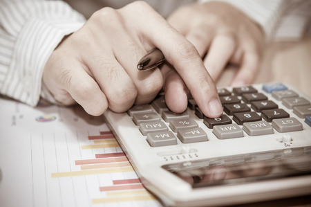 contaduria: business man hand with Calculator and business report.