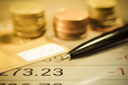 capital gains: pen and money coin pile. finance and banking concept.