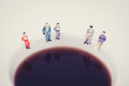 miniature people: miniature people business team sitting on white coffee cup having a coffee break. business idea concept