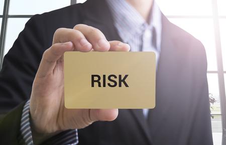 hazardous work: businessman hand holding a business card with a message risk management to success concept.