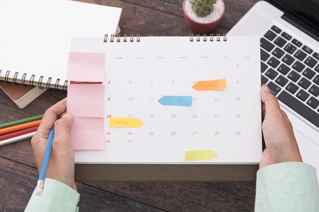 open adult agenda: Business women checking appointments in the calendar on desk work at the office.