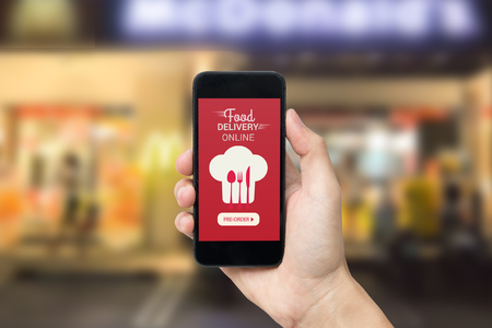 Hand holding smart phone with food delivery order screen on blur of restaurant background Standard-Bild