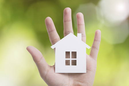 ownerships: hand holding home on green nature background. Stock Photo