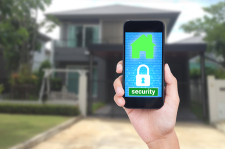 Hand holding mobile phone with concept technology home security system. Imagens