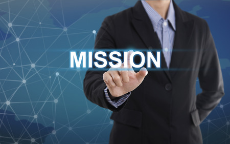 virtual assistant: Businessman hand pressing button mission. sign on virtual screen. business concept. Stock Photo