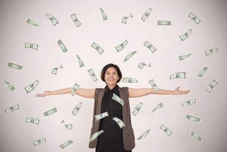 happy woman celebrates success under a money rain falling dollar bills banknotes on wall background
