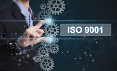 Businessman hand select wording iso 9001. sign on virtual screen. business concept.