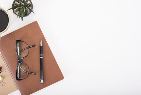 ノートブック、ペン、紙の本とコーヒーのカップを持つモダンなオフィス デスク。トップ ビューのテーブル上から入力テキストをコピー スペース