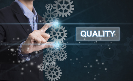 Businessman hand select wording quality. sign on virtual screen. business concept. Stockfoto