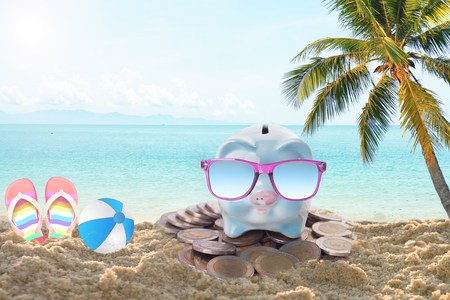 travel piggy bank with sunglasses relax on the beach holiday. concept saving money for travel in holiday Stock Photo